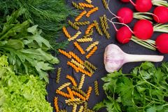Uncooked pasta with fresh vegetables and herbs. Raw ingredients for making pasta including fresh lettuce, arugula, dill, parsley, garlic and radish. Detox your Royalty Free Stock Image