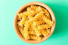 Uncooked pasta fusilli in a wooden bowl . On turquoise background stock photos