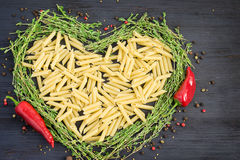 Uncooked pasta laid out in the shape of a heart and decorated Stock Photos