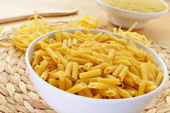 Uncooked pasta. Some different uncooked pasta, such as penne rigate, tagliatelle and pastina, on a table Stock Image