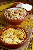 Uncooked pasta, spaghetti alla carbonara and grated cheese Stock Photo