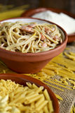 Uncooked pasta, spaghetti alla carbonara and grated cheese Stock Photos