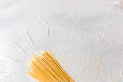 Uncooked pasta spaghetti on floured white background. Hand drawn sun beams on table, simple style. Uncooked pasta spaghetti close-up on floured white background Stock Photography