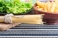 Uncooked pasta and spaghetti with green salad close-up Stock Photography