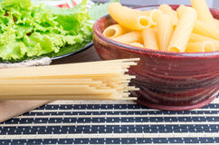 Uncooked pasta and spaghetti with green salad Stock Photo