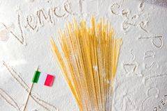 Uncooked pasta spaghetti and italian flag close-up on floured white background. Travelling to Italy back concept. Uncooked pasta spaghetti and italian flag close Stock Images