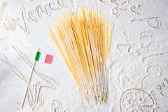 Uncooked pasta spaghetti macaroni and italian flag on floured white background. Food travel italian cuisine concept. Uncooked pasta spaghetti macaroni and Royalty Free Stock Images