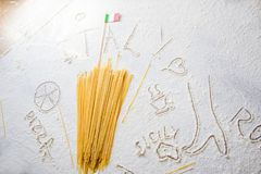 Uncooked pasta spaghetti macaroni and italian flag on floured white background. Food travel italian cuisine concept. Uncooked pasta spaghetti macaroni and Stock Images