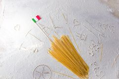 Uncooked pasta spaghetti macaroni and italian flag on floured white background. Words Italy, Rome, Sicily and Pasta written in flour from hand, hand drawn Stock Photo