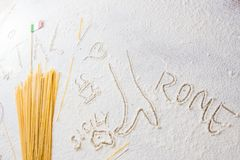 Uncooked pasta spaghetti macaroni and italian flag on floured white background. Words Italy, Rome, Sicily and Pasta written in flour from hand, hand drawn Stock Image