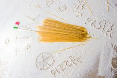 Uncooked pasta spaghetti macaroni and italian flag on floured white background. Words Italy, PIZZA and PASTA written in flour from hand, hand drawn a cup of Royalty Free Stock Image