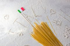 Uncooked pasta spaghetti macaroni and italian flag on floured white background. Words ITALY written in flour from hand, hand drawn hearts, a cup of coffee Royalty Free Stock Photography
