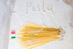 Uncooked pasta spaghetti macaroni and italian flag on floured wood table. Word Pasta written in flour from hand. Uncooked pasta spaghetti macaroni and italian Stock Photo