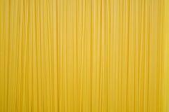 Uncooked pasta spaghetti macaroni yellow background. Textured royalty free stock photos