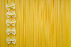 Uncooked pasta spaghetti macaroni yellow background, textured.  royalty free stock photo