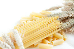 Uncooked pasta and spaghetti with wheat ears. Closeup Stock Photos