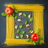 Uncooked pasta, tomato an spices as picture background. Top view Royalty Free Stock Photography