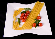 Uncooked pasta and tomatoes. Bowl of uncooked pasta, tomatoes, and basil on black background Stock Photos