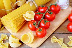 Uncooked pasta and tomatoes Stock Photo