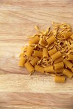 Uncooked pasta on warm wood background. Stock Images
