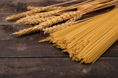 Uncooked pasta and wheat ears Royalty Free Stock Photography