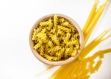 Uncooked pasta in a wooden bowl. royalty free stock images
