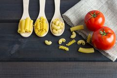 Uncooked pasta in a wooden spoon stock photo