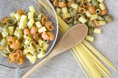 Uncooked pasta with wooden spoon Royalty Free Stock Image