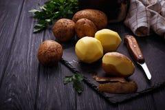 Uncooked peeled potatoes on dark background Royalty Free Stock Image