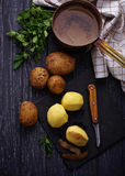 Uncooked peeled potatoes on dark background Royalty Free Stock Photography