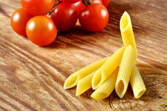 Uncooked penne pasta and cherry tomatoes Stock Images