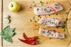 Uncooked pieces of silver carp fish with red chile pepper, bay leaf, apple, spices and garlic on wooden board, top view. Royalty Free Stock Images