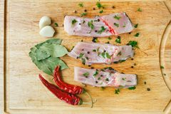 Uncooked pieces of silver carp fish with red chile pepper, bay leaf, spices and garlic on wooden board, top view. Stock Images