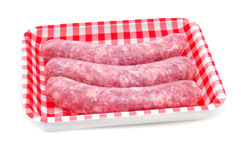 Uncooked pork meat sausages. A pile of uncooked pork meat sausages in a plastic tray on a white background Royalty Free Stock Photo