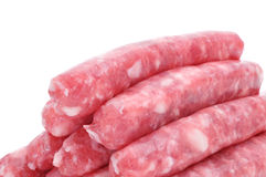 Uncooked pork meat sausages. A pile of uncooked pork meat sausages on a white background Royalty Free Stock Photo