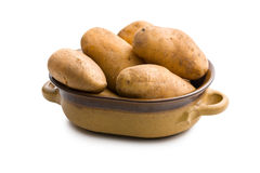 Uncooked potatoes in ceramic pot Stock Photos