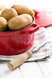 Uncooked potatoes and old wooden peeler Stock Photos