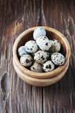Uncooked quail eggs in the wooden bowl Royalty Free Stock Image