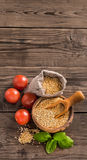 Uncooked quinoa with tomatoes vertical Stock Photo
