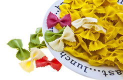 Uncooked rainbow farfalle pasta on plate Stock Photos