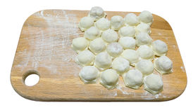 Uncooked ravioli ravioli on a wooden board.  Stock Image