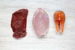 Uncooked raw beef meat, turkey breast and salmon steak on white wooden background, top view. Flat lay Stock Photo