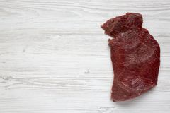 Uncooked raw beef meat on white wooden background, top view. Flat lay. From above. Copy space Stock Photography
