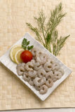 Uncooked raw headless Shrimps with lemon slice and tomato on white plate with Bamboo matt. Creative food photography on studio background Stock Photo