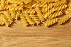 Uncooked raw pasta background on wooden background. Raw pasta macaroni background on wooden texture royalty free stock photo