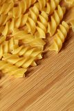 Uncooked raw pasta background on wooden background. Raw pasta macaroni background on wooden texture royalty free stock images