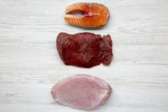 Uncooked raw salmon steak, beef meat and turkey breast on white wooden background, top view. Flat lay. Copy space Stock Photography