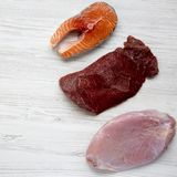 Uncooked raw salmon steak, beef meat and turkey breast on white wooden table, overhead view. Flat lay. From above. Close-up royalty free stock photo
