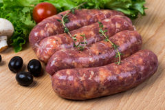 Uncooked raw sausages on wooden board. Uncooked raw sausages with lettuce, tomatoes, mushrooms on wooden board Stock Photo