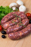 Uncooked raw sausages on wooden board. Uncooked raw sausages with lettuce, tomatoes, mushrooms on wooden board Stock Photography